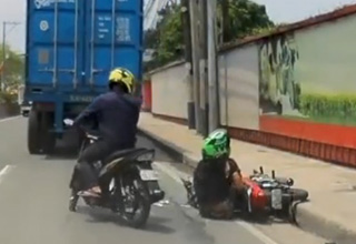 a man in a green helmet and black shirt crashed his motorcycle and other bikers are stopping to help him