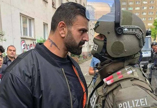 a very tall man face to face with cop in riot gear