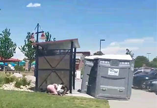 a portable potty on a sidewalk with a lady next to it who is crouching down
