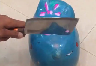 a man holding a meat cleaver breaks open a blue piggy bank