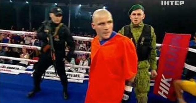 bald boxer walks into the ring hand cuffed
