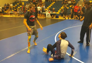 an older jiu jitsu fighter towers over a younger opponent sitting on the mat