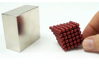 a square chrome colored magnet and a stack of red ball magnets being pulled toward them