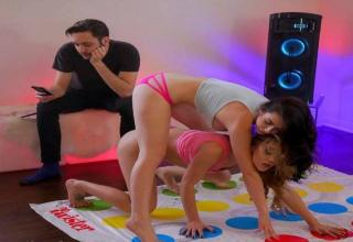girls playing twister while a man looks at his phone