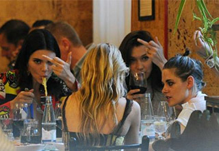 emma watson sitting with her friends who are flicking off a camera guy