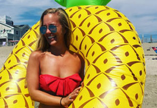 a busty woman in red bikini and pineapple float