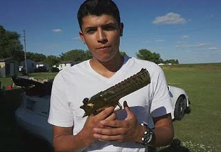 Mexican kid holding a gun in a field