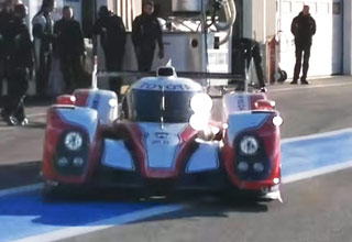 a toyota hybrid race car in front of a group of people