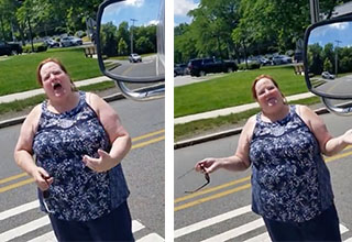 A woman wearing a blue pattered dress is blocking the roadway as she yells at a bus driver. She is holding her arms out and her mouth is wide open.