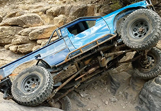 A blue Toyota 4wd truck is climbing over a technical rock obstacle on an off-road trail in Colorado. It is going sideways on two wheels as it climbs over this incredible obstacle with people cheering in the background.