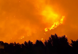 The Lake Christine Fire in Colorado rages in the background. It had grown to over 8,300 acres by July 6, according to CBS Denver. The Eagle County Sheriff's Office reported the fire was zero-percent contained. Erratic winds were making the fire unpredicta