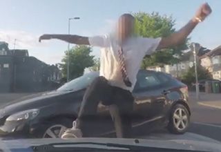 An English man wearing a button-down shirt and tie is slamming his foot on the hood of a car with his car parked in the background on a street in England.