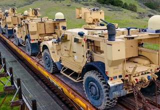 a drone films a train carrying hundreds of military vehicles and equipment