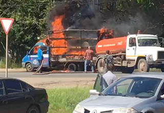 A blue truck is on fire on the side of a road in Russia. Another truck carrying sewage is attempting to extinguish the flames.