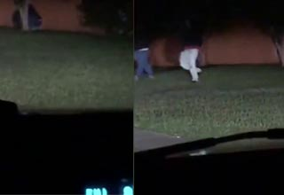 two guys prowling across a residential yard