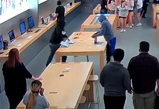 two men grabbing laptops in the middle of a crowded apple store