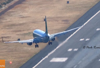 a large jumbo jet flying sideways over the runway due to heavy cross winds