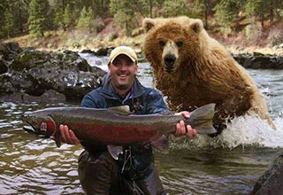bear sneaking up on a guy holding a fish