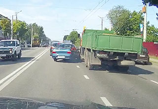 A blue sedan is seen turning into a green truck on a roadway in Russia. The blue car did not see the truck as it was changing lanes, causing a multi-car accident.