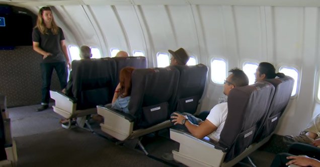 a man talks to passengers on an airplane