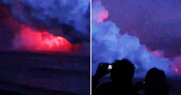 a cloud of smoke erupting above lava hitting the water as people take photos