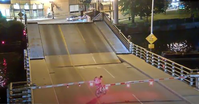 a draw bridge raising as a person on a bike approaches