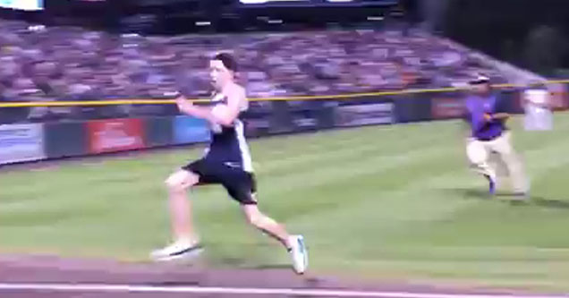 a guy running from a security guard on the field of a baseball stadium