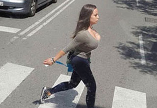a very busty girl walking through the crosswalk