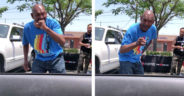 An older black man is standing outside of a guy's car window pretending to hold a microphone and performing a freestyle rap.