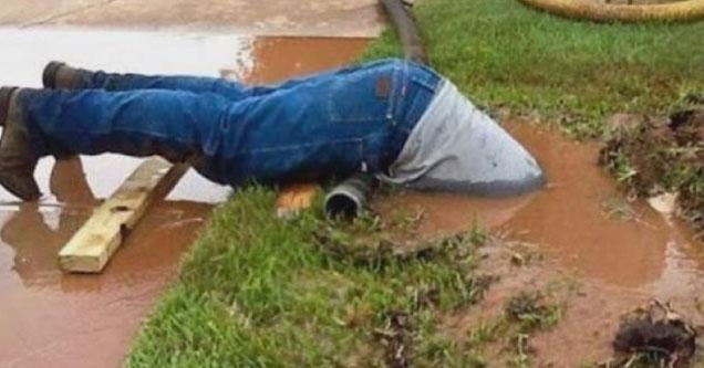 plumber half way in a pile of mud