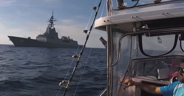 a huge navy warship pulls up alongside a small fishing boat