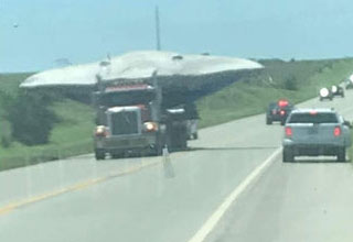 a truck transporting an f-35 plane that looks like a UFO