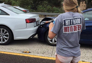 a girl wearing a shirt that says hit it hard and hit it often standing by a car accident