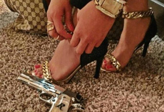 a woman with gold jewelery and a gun on the floor