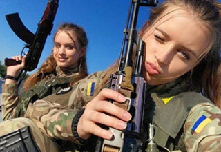 two attractive female soldiers holding ak-47s