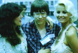 a young bill gates with two attractive women