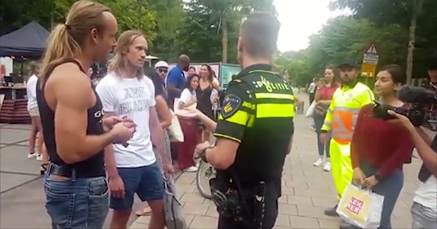 a man with a pony tail standing in front of a police officer and a vegan holding a blob of raw meat in amsterdam