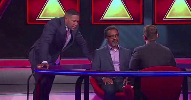 Tim Meadows and Michael Strahan staring at a man who is sitting on the set of 100000 dollar pyramid