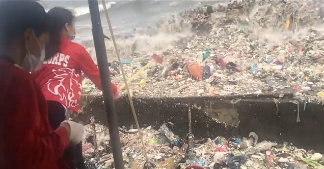 Volunteers in Manila Bay, Philippines struggle to clean up garbage washing ashore on August 11, 2018.