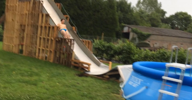 a man in a blue speedo going down a homemade water slide