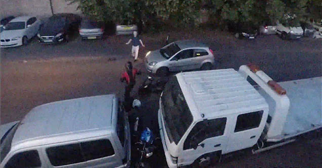 Two thieves attempting to steal a motorbike are approached by a man who just got out of his car.