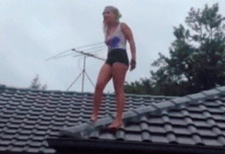a blonde girl in tight booty shorts and a tank top standing on the roof