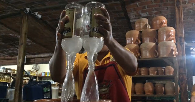 A man in Tequila, Mexico pours two bottles of tequila into a massive drink that costs $100 and serves a whole table.