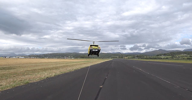 a car with helicopter blades is hovering just above the ground in Llandedr, UK in 2018. It is attached to a rope that is being pulled at hight speed by a truck down an airport runway.
