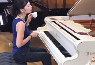 a woman in a blue shirt and blue jeans drinking a white cup of tea and sitting at a white grand baroque piano