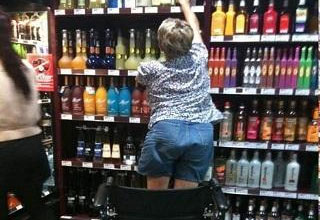 a women getting out of her wheelchair to grab alcohol off the shelf