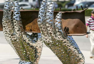 a memorial for september 11th that's a pair of shiny metal hands made of doves hold a steel beam from the twin towers