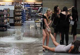 a store with water shooting out in it, a lady being grabbed by her friend and falling down