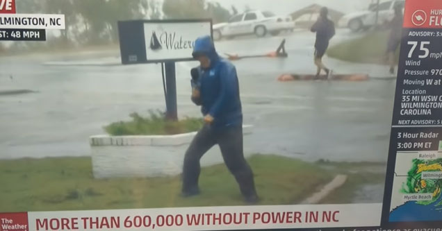 a reporter struggling to stay standing in hurricane florence while two men casually walk by him