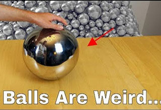 a giant silver ball sitting on a wooden desk